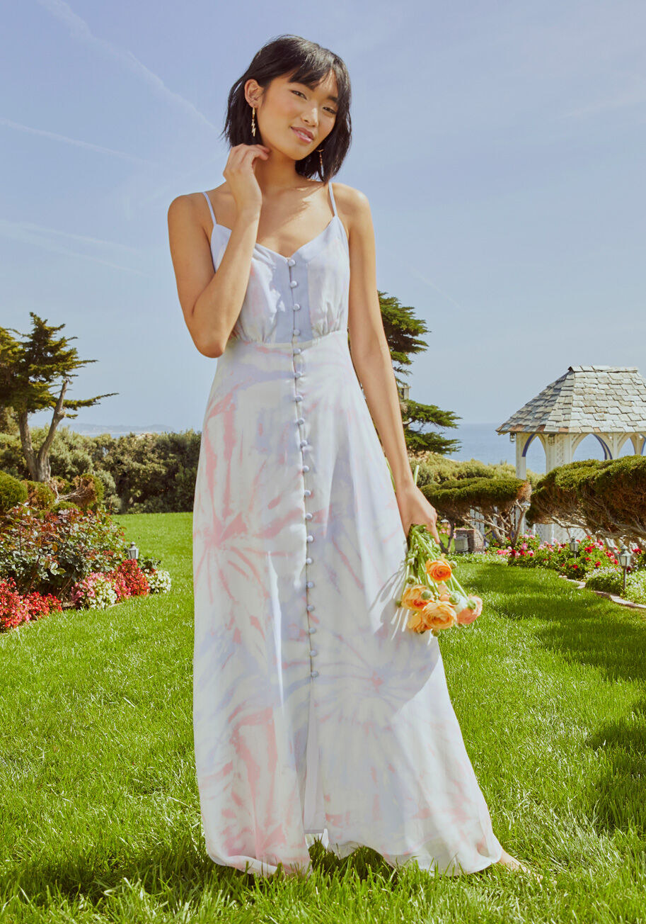 Model wearing the dress, featuring a long row of button closures beneath a V-neckline and sleeveless silhouette