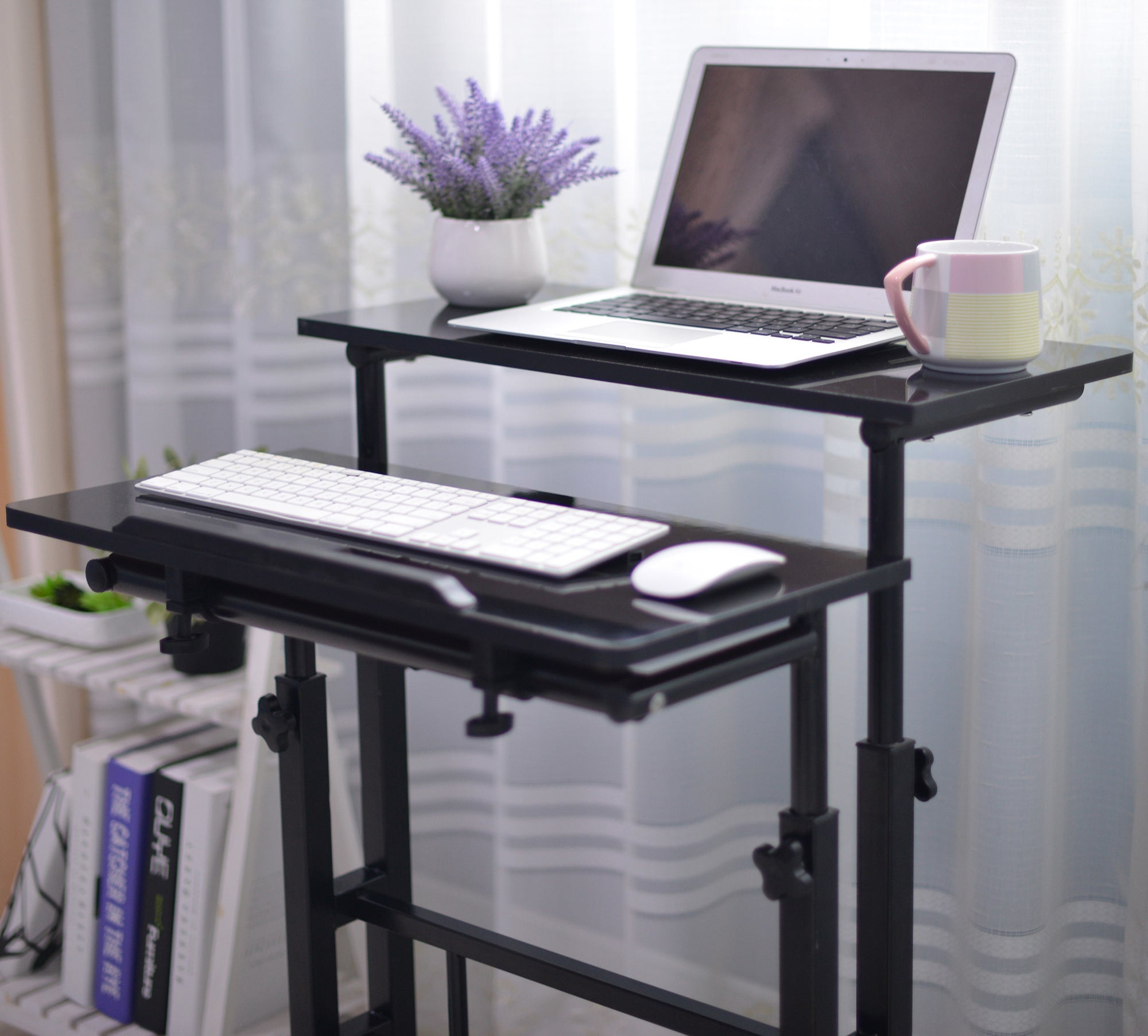 A black standing desk with a spot for a laptop and an adjustable pull out shelf for a keyboard