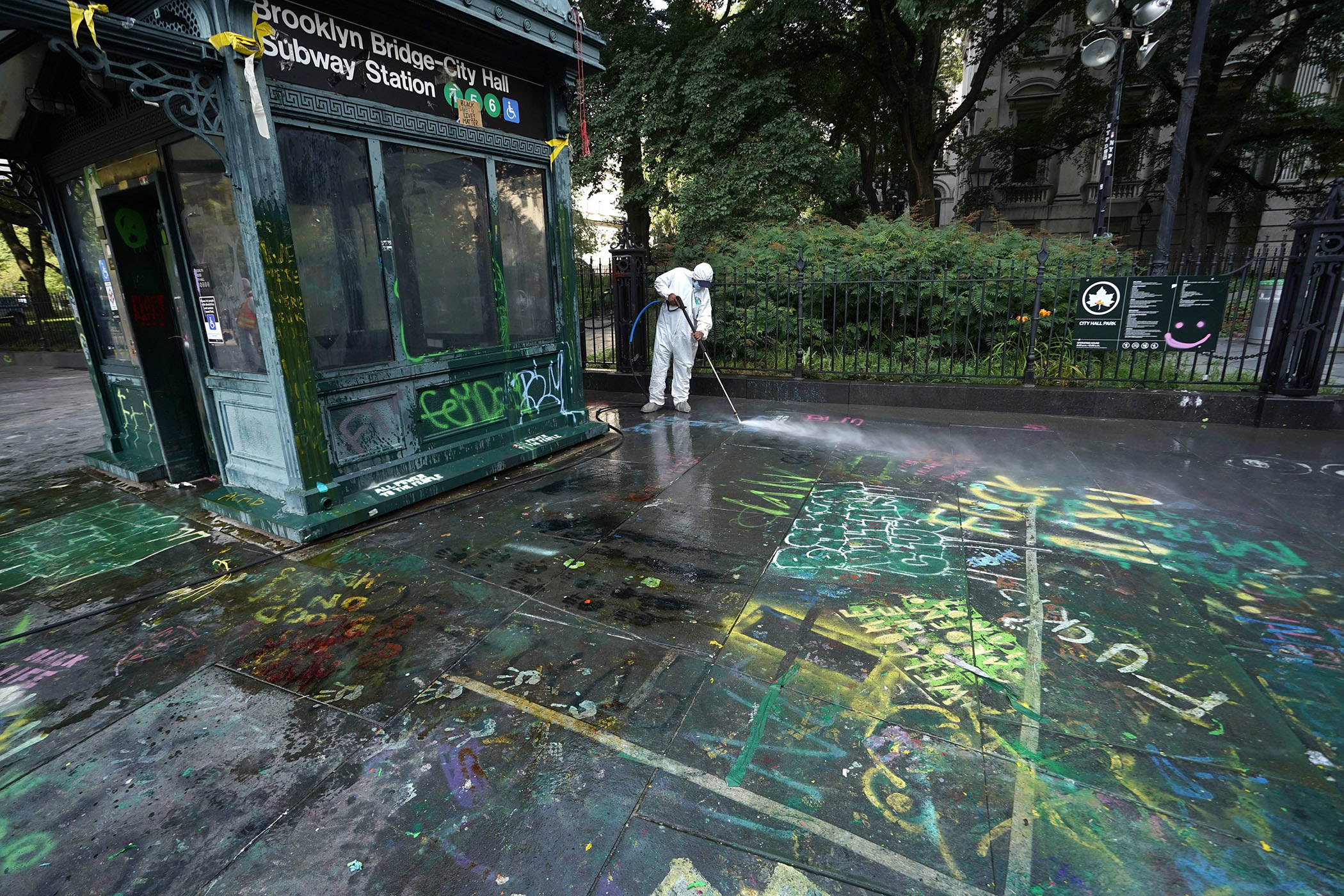 A sanitation worker dressed in an all-white uniform washes graffiti on the ground outside the Brooklyn Bridge–City Hall Subway Station