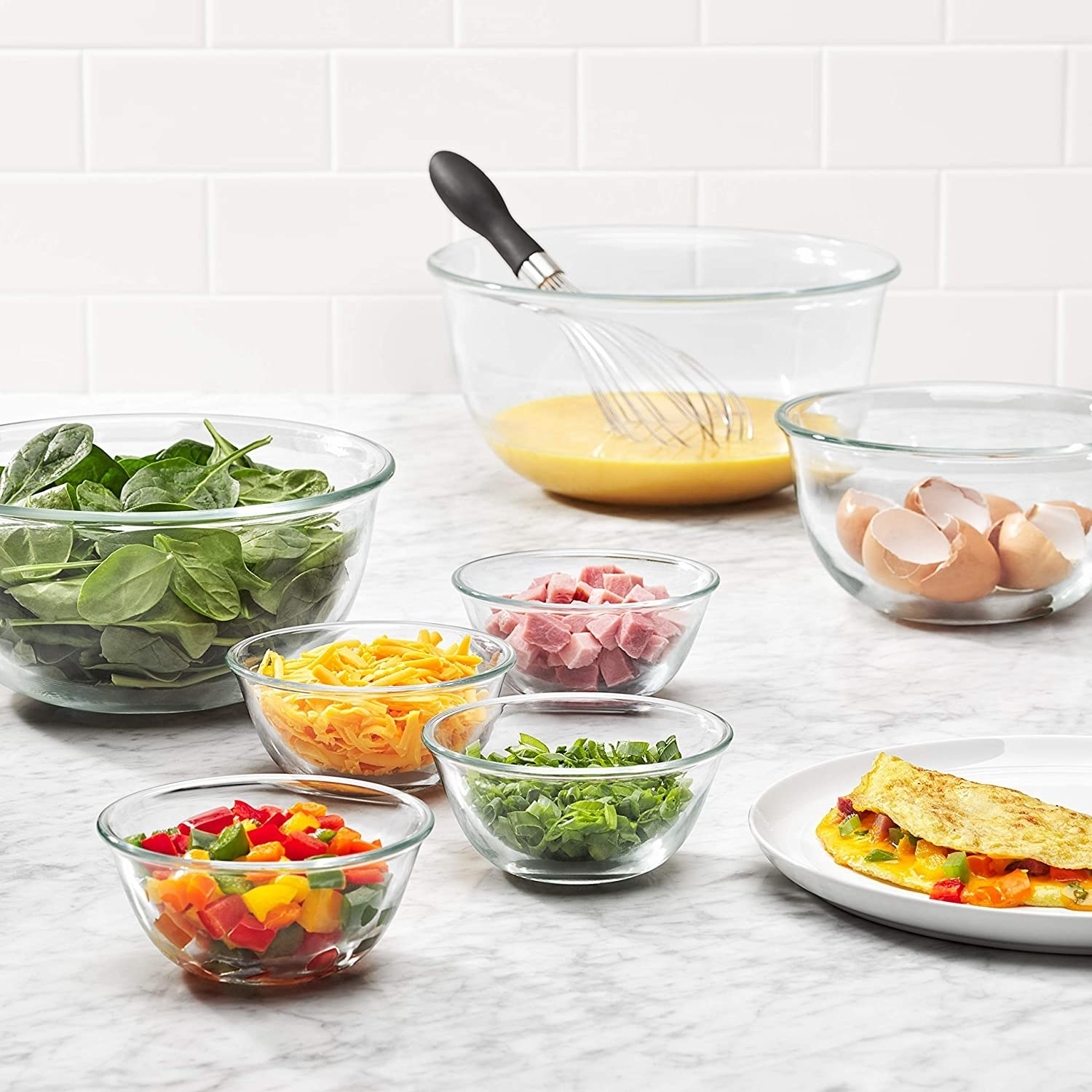 The bowls in an omelet prep station, each with different ingredients in them