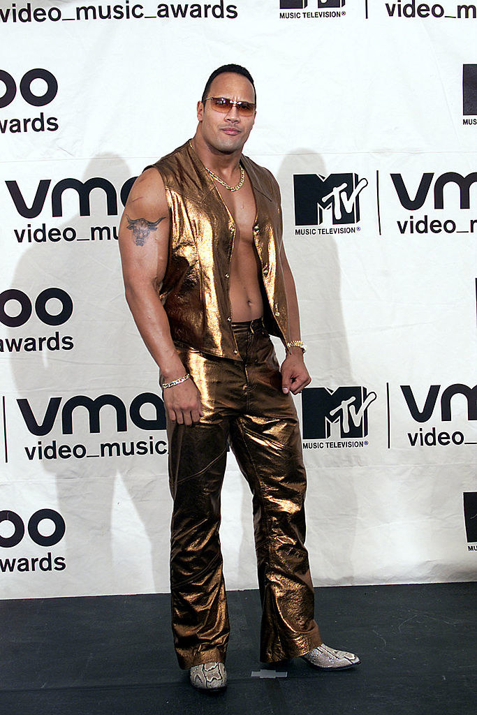 the rock wearing gold latex clothing with an exposed chest