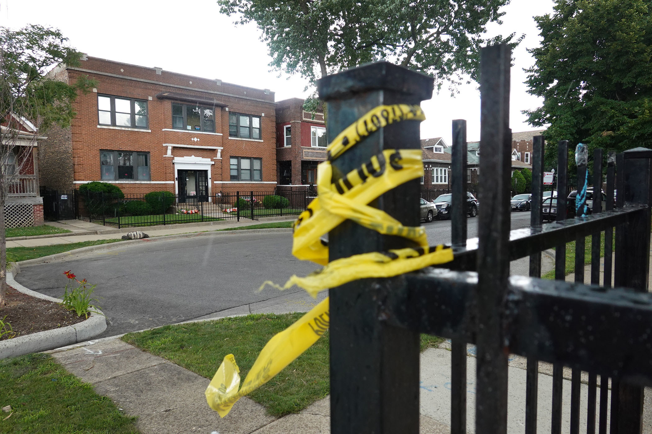 Yellow caution tape is wrapped around an iron fence; in the background, an empty street and brick buildings