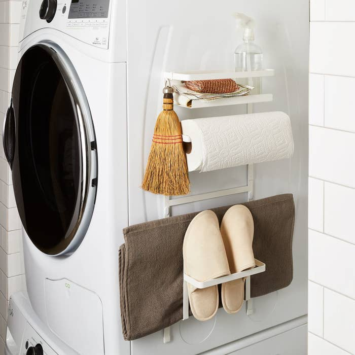 Magnetic rack on side of washing machine holding slippers and broom