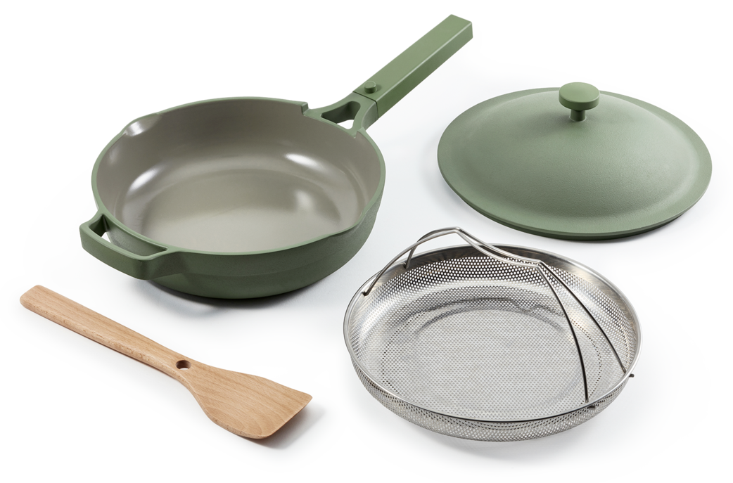 The pan in sage green with steamer basket and spatula
