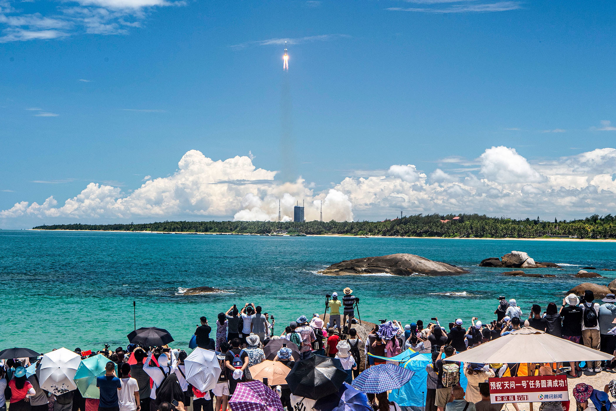 A crowd of people stand near the shore to watch a rocket launch in the distance; many of the people take pictures and shade themselves under umbrellas