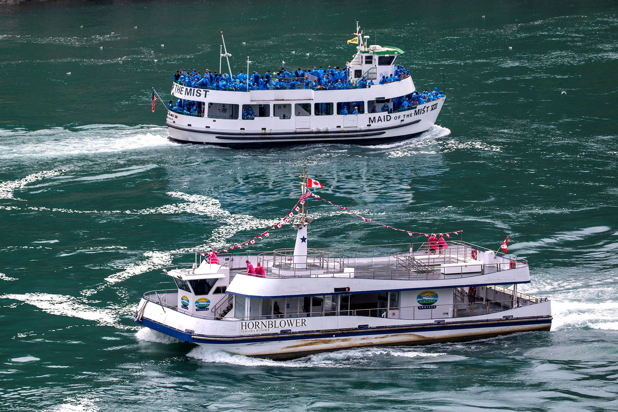 "One boat in the foreground, named Hornblower, carries six passengers dressed in bright red raincoats; in the background, a tourist boat named ""Maid of the Mist"" carries several dozen passengers in blue raincoats"