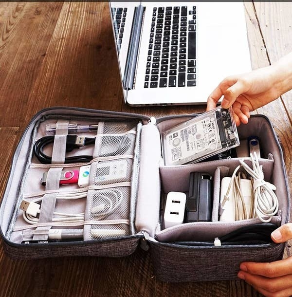 A person using the organiser to neatly store chargers, cables, pen drives, and other tech accessories.