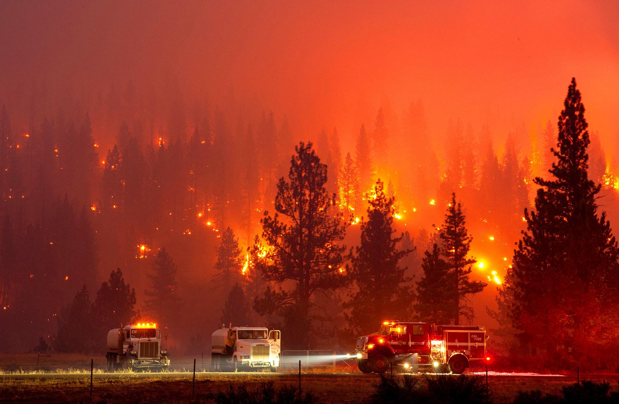 A fire burns through a hillside with trucks parked in a field below