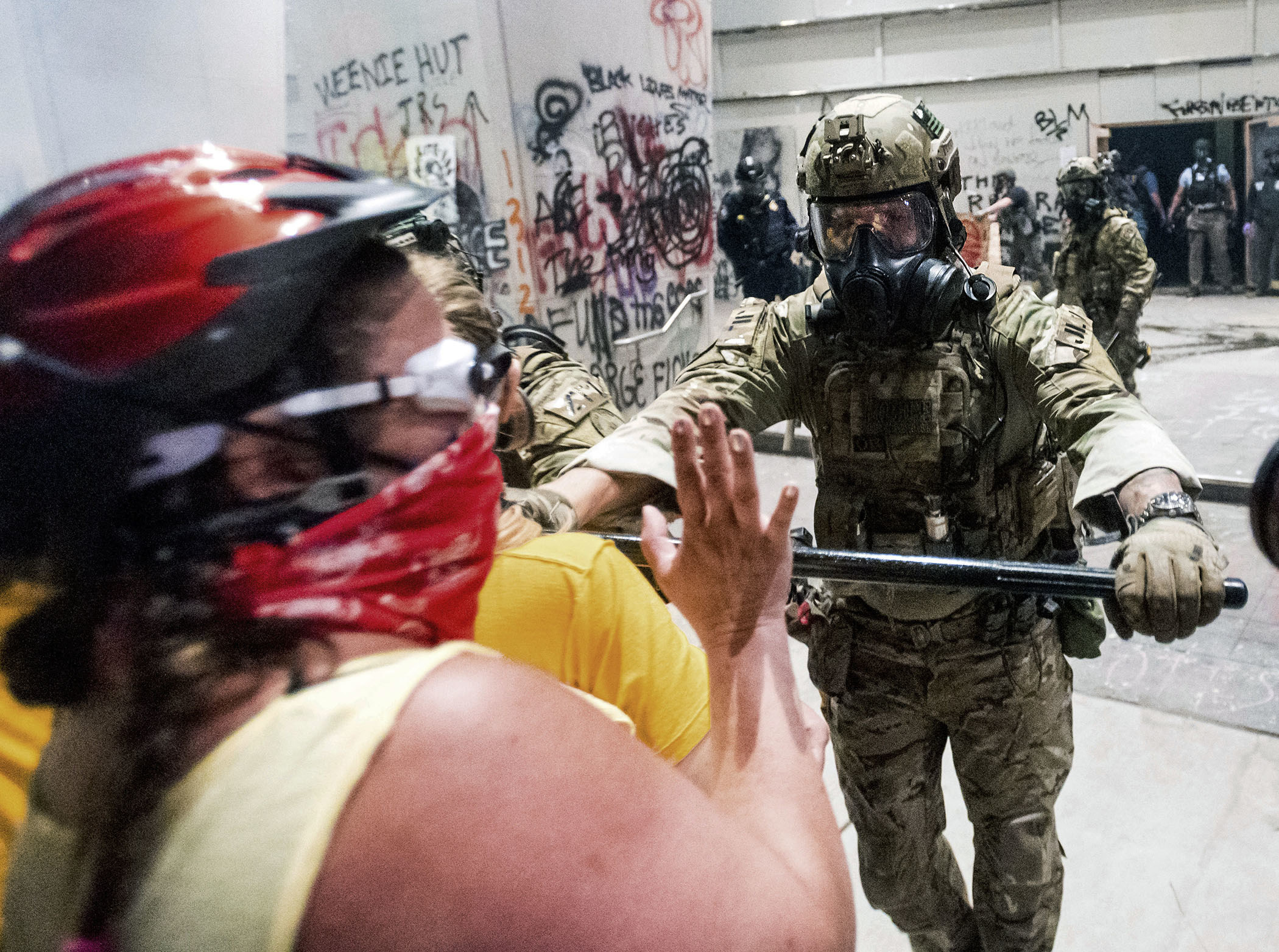 A federal officer, dressed in camouflage with a gas mask on, uses a baton to push against a demonstrator, who wears a red helmet and red bandana over her face