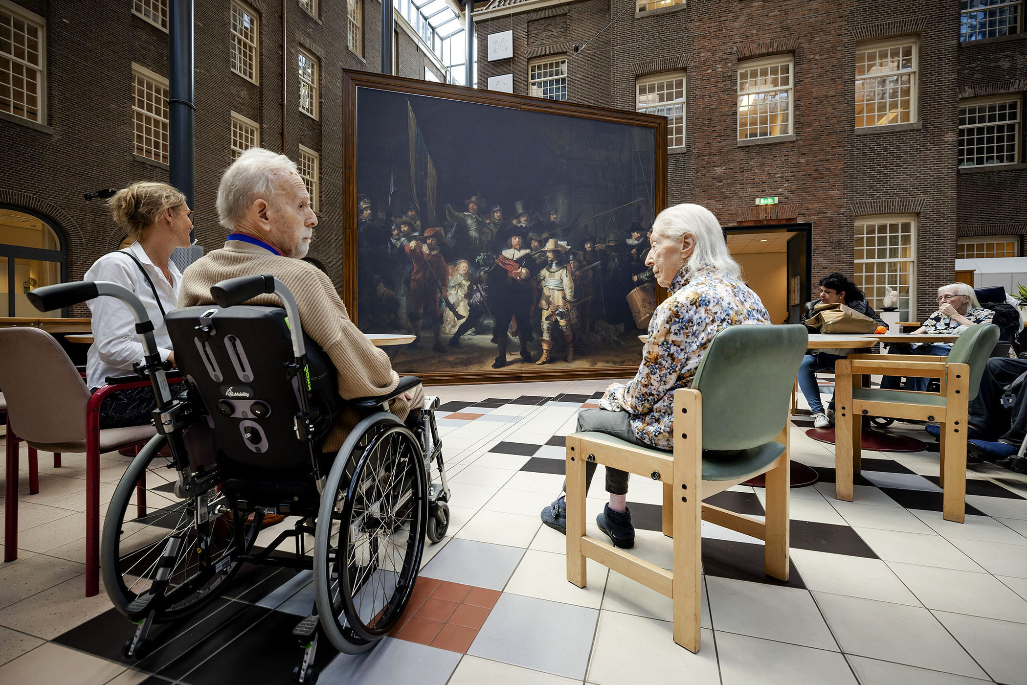 Older people sit in wheelchairs and in seats around a large Rembrandt painting,