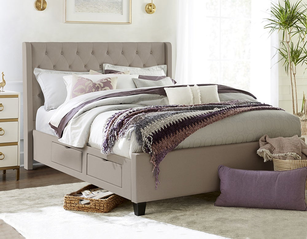 A raised gray queen sized bed frame with shelving in it