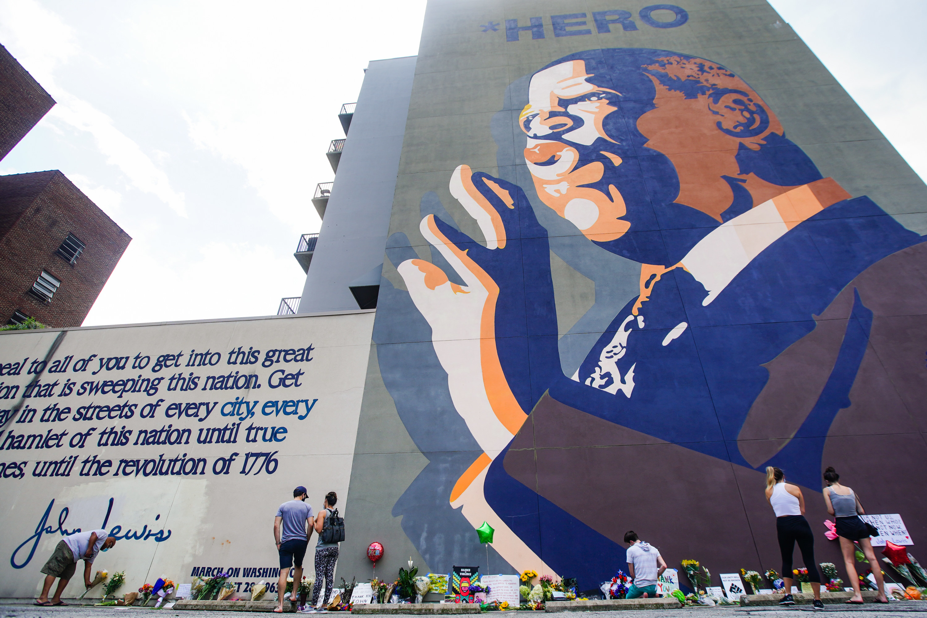 "People leave flowers, balloons, and cards, on the ground beneath a towering mural of Rep. John Lewis that says the word ""Hero"" at the top"