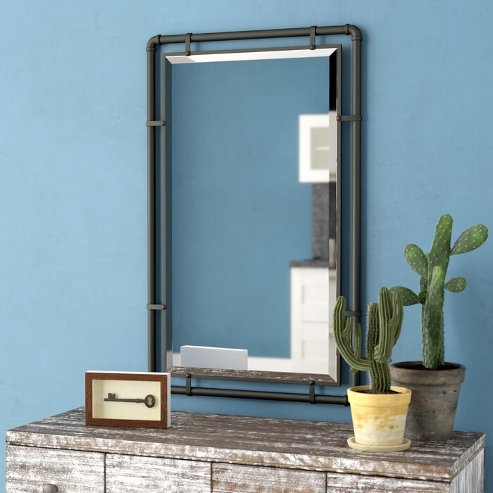 The Koeller Industrial Metal Wall Mirror hung in a bedroom