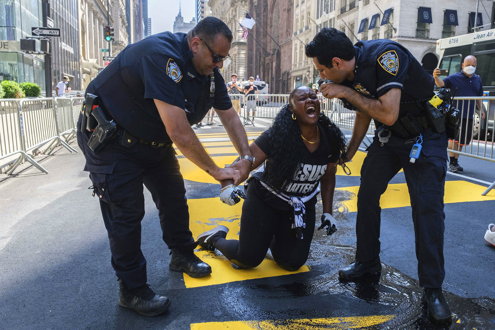 Two police officers hold onto the arms of a screaming woman kneeling on the ground