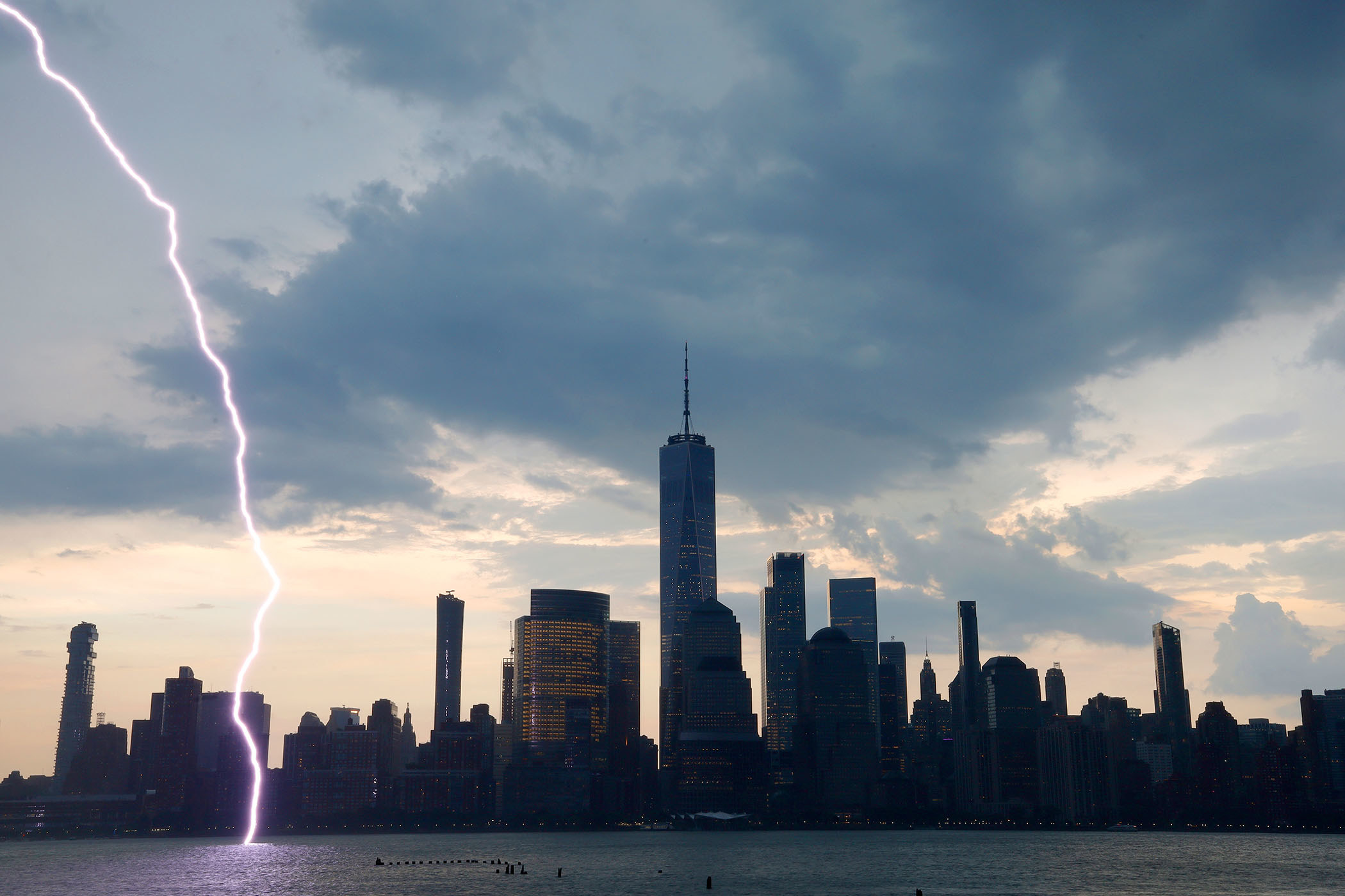 Lightning strikes the Hudson River; the skyline of buildings in New York's Financial District stands in the background