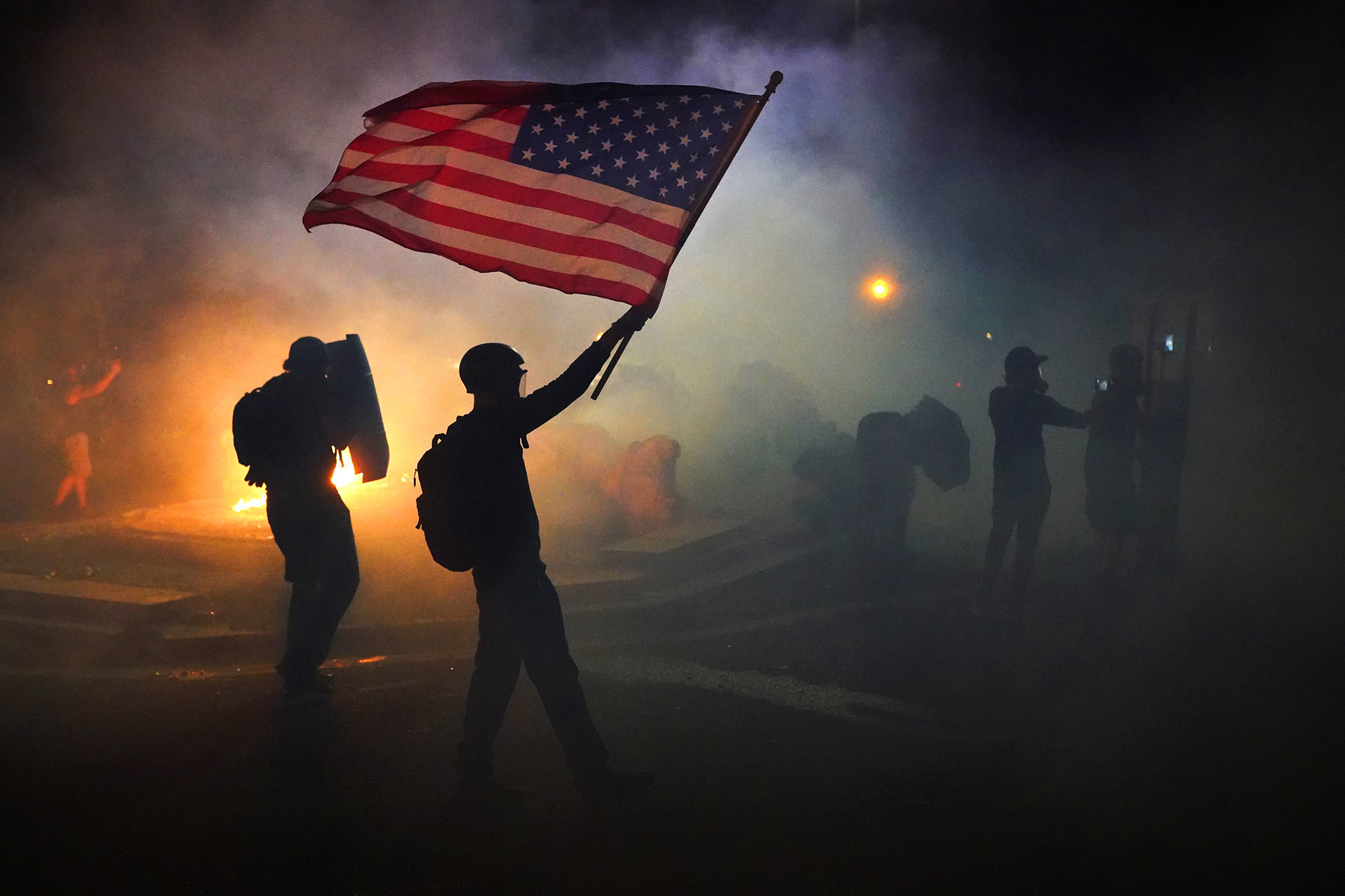 A demonstrator, backlit by a fire in the background, holds up a US flag amid clouds of tear gas