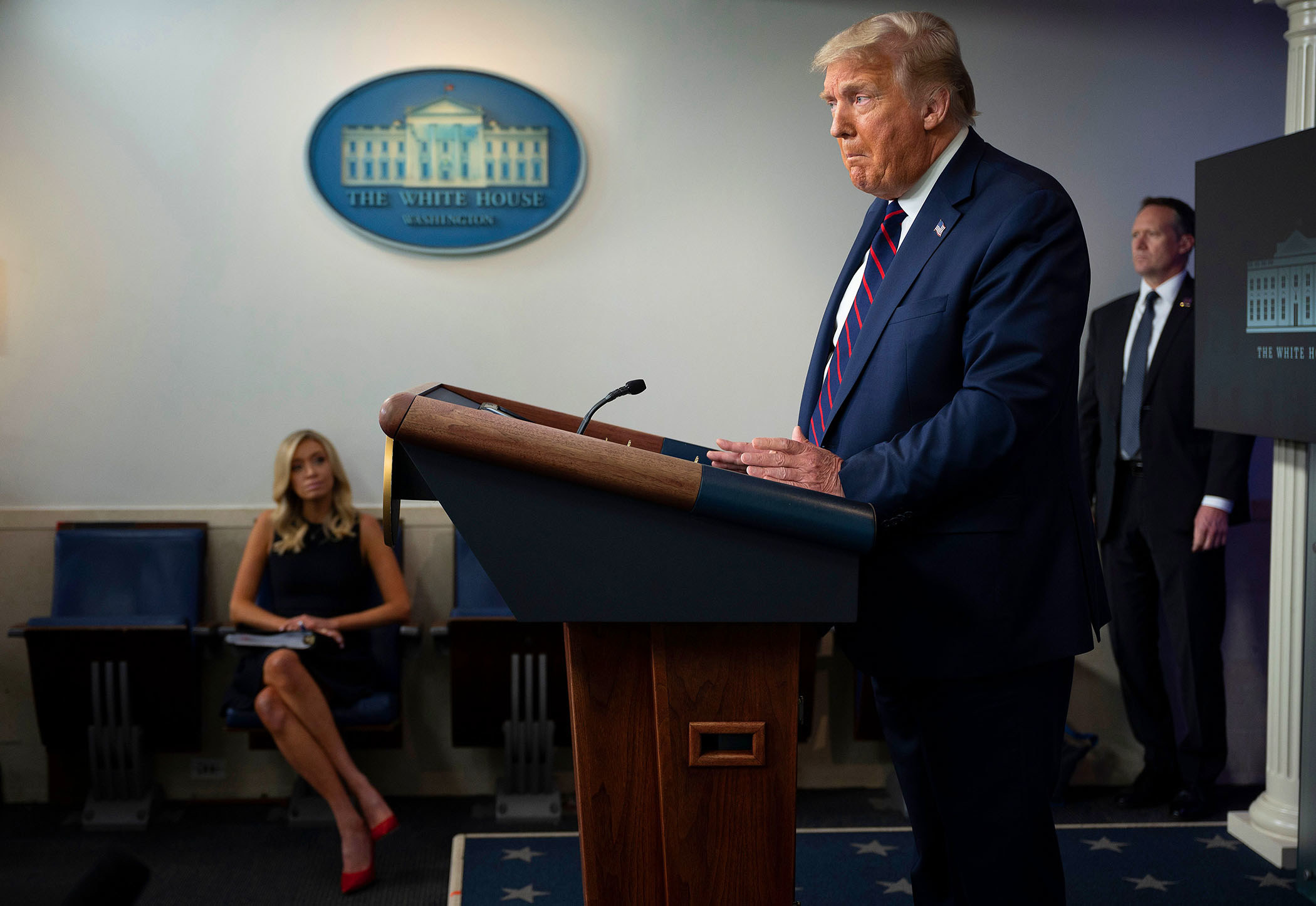President Trump stands behind a lectern while press secretary Kayleigh McEnany sits in the background