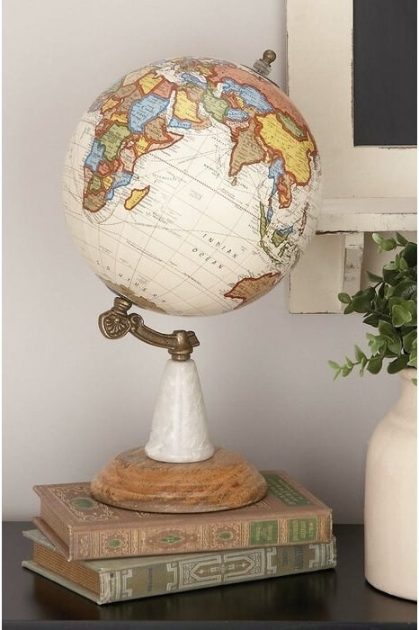 The Wood Metal Marble Globe perched on two vintage books
