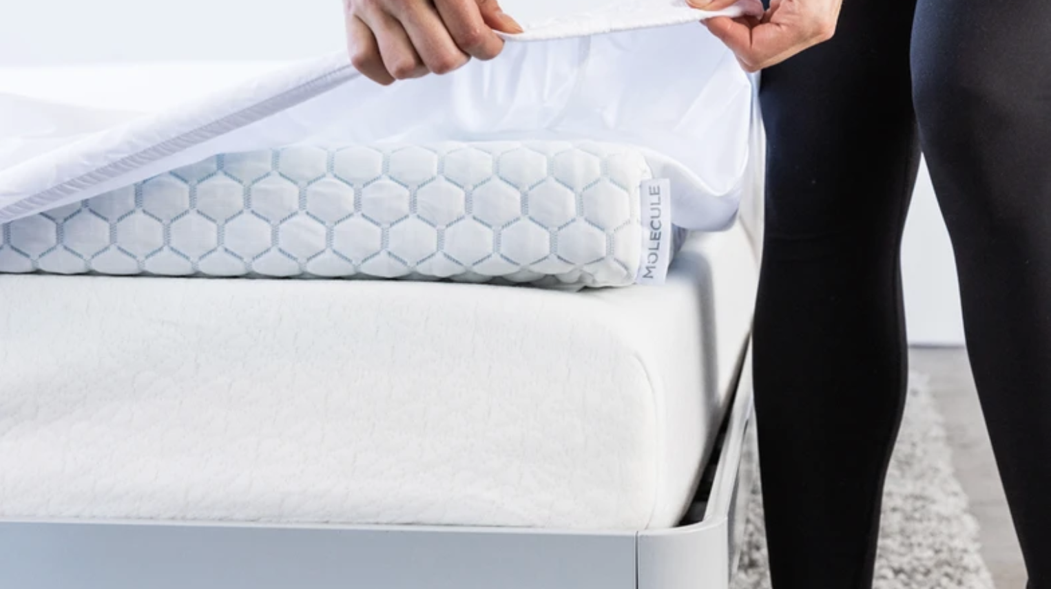 A model placing the mattress topper on a bed