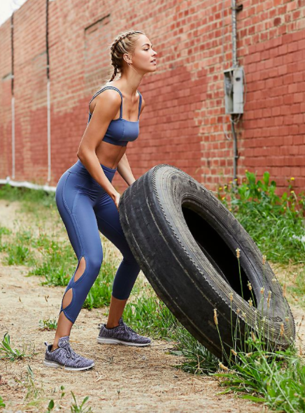 Model moves tire while wearing three-quarter blue workout leggings and a bra