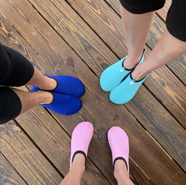 A reviewer photo of three people wearing the water shoes in light pink, blue, and turquoise