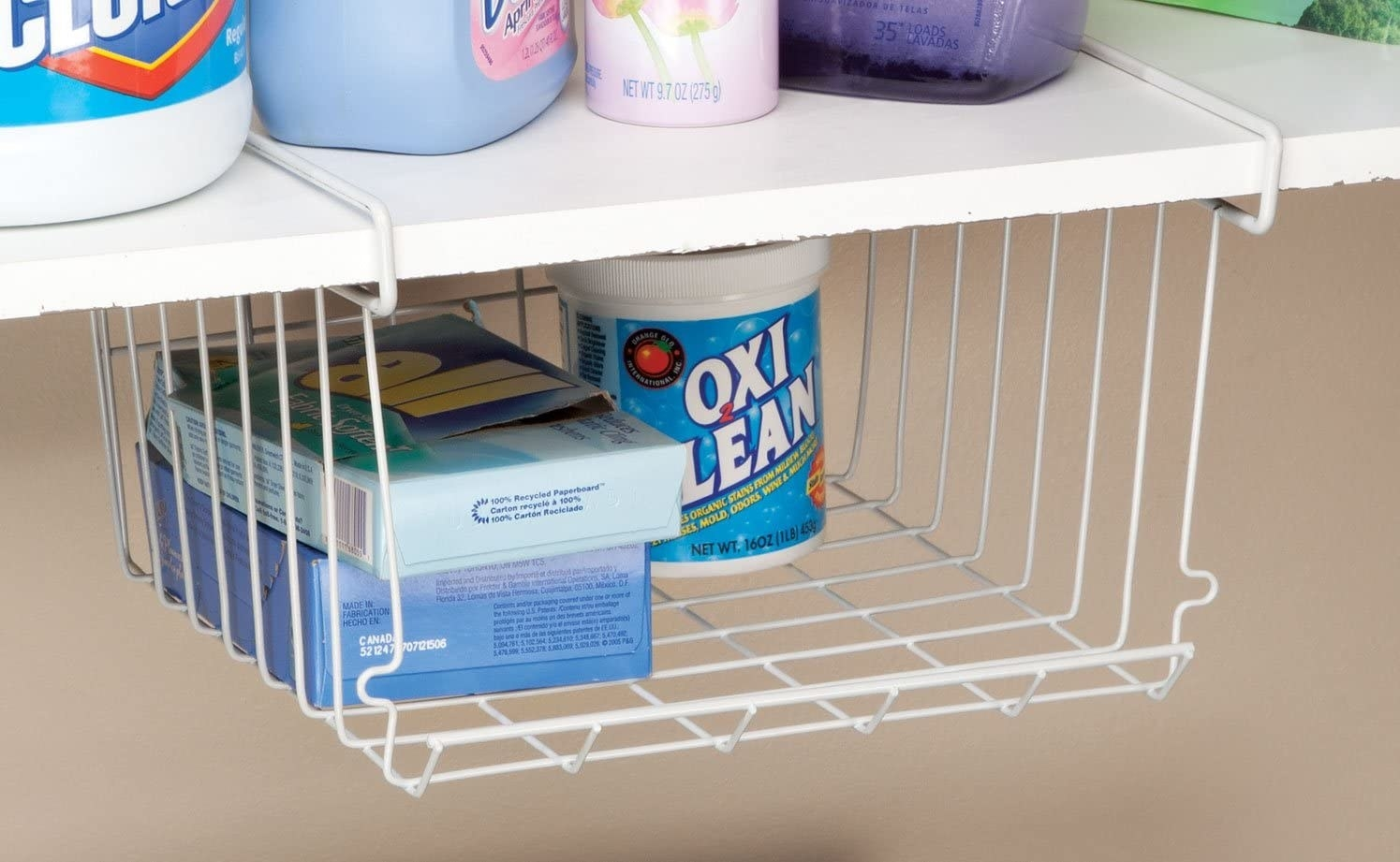the wire shelf in a laundry room hanging from a wood shelf
