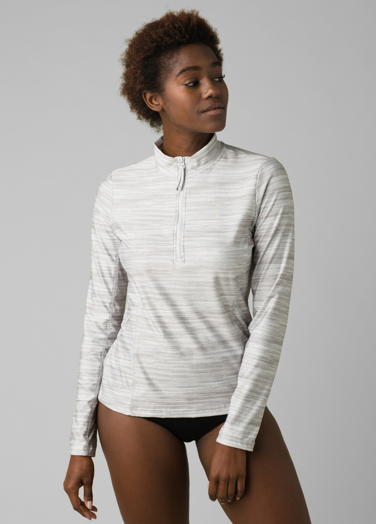 model in gray and white irregular stripe long-sleeve top with a quarter zip