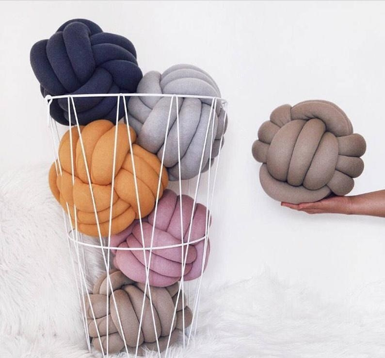 Five knot pillows in a bask and one in a model's hand