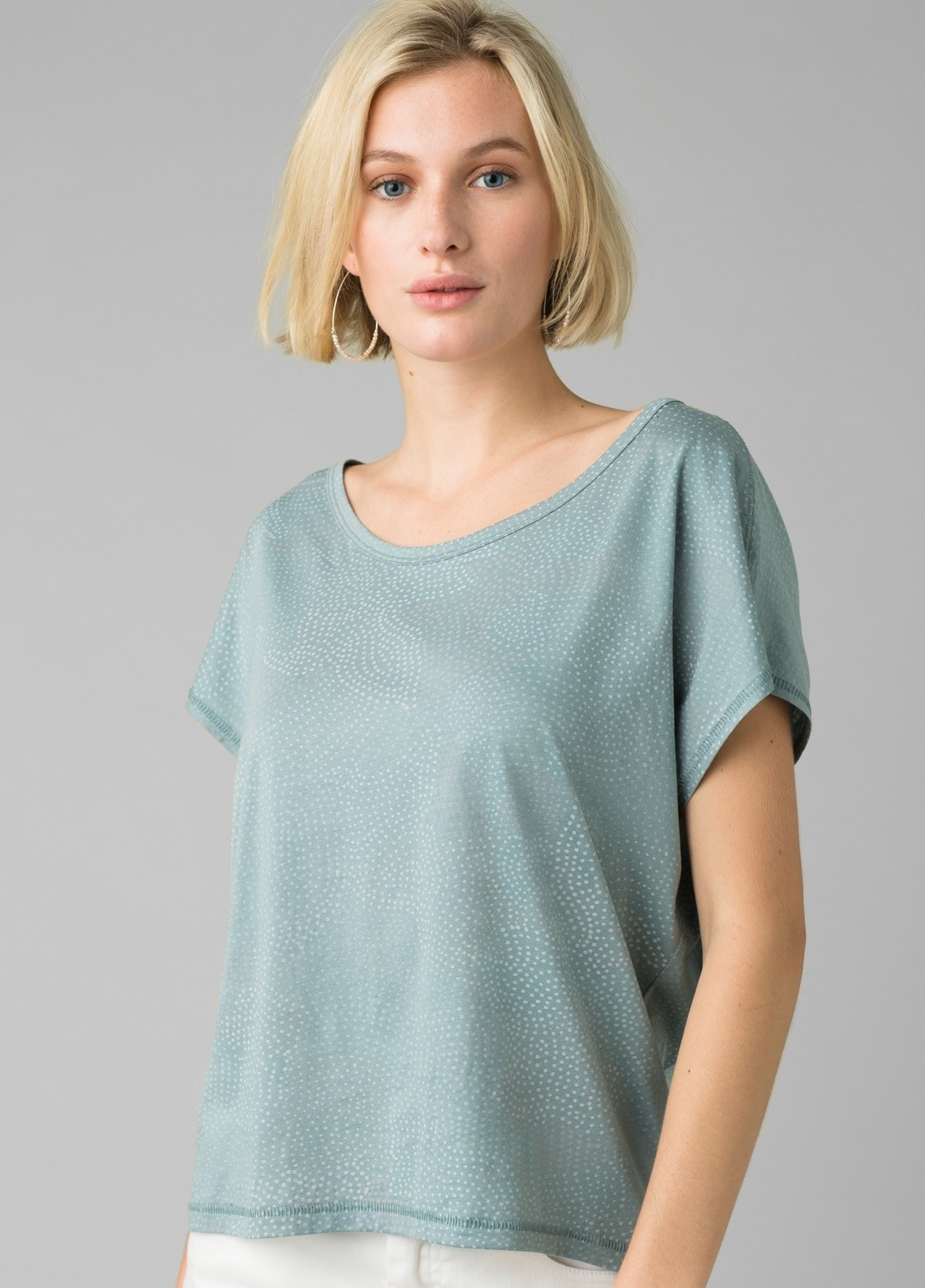 model in light teal wide crew neck tee with small lighter blue speckles