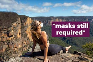 Hiker takes a break on a cliff overlooking valley while wearing a face mask