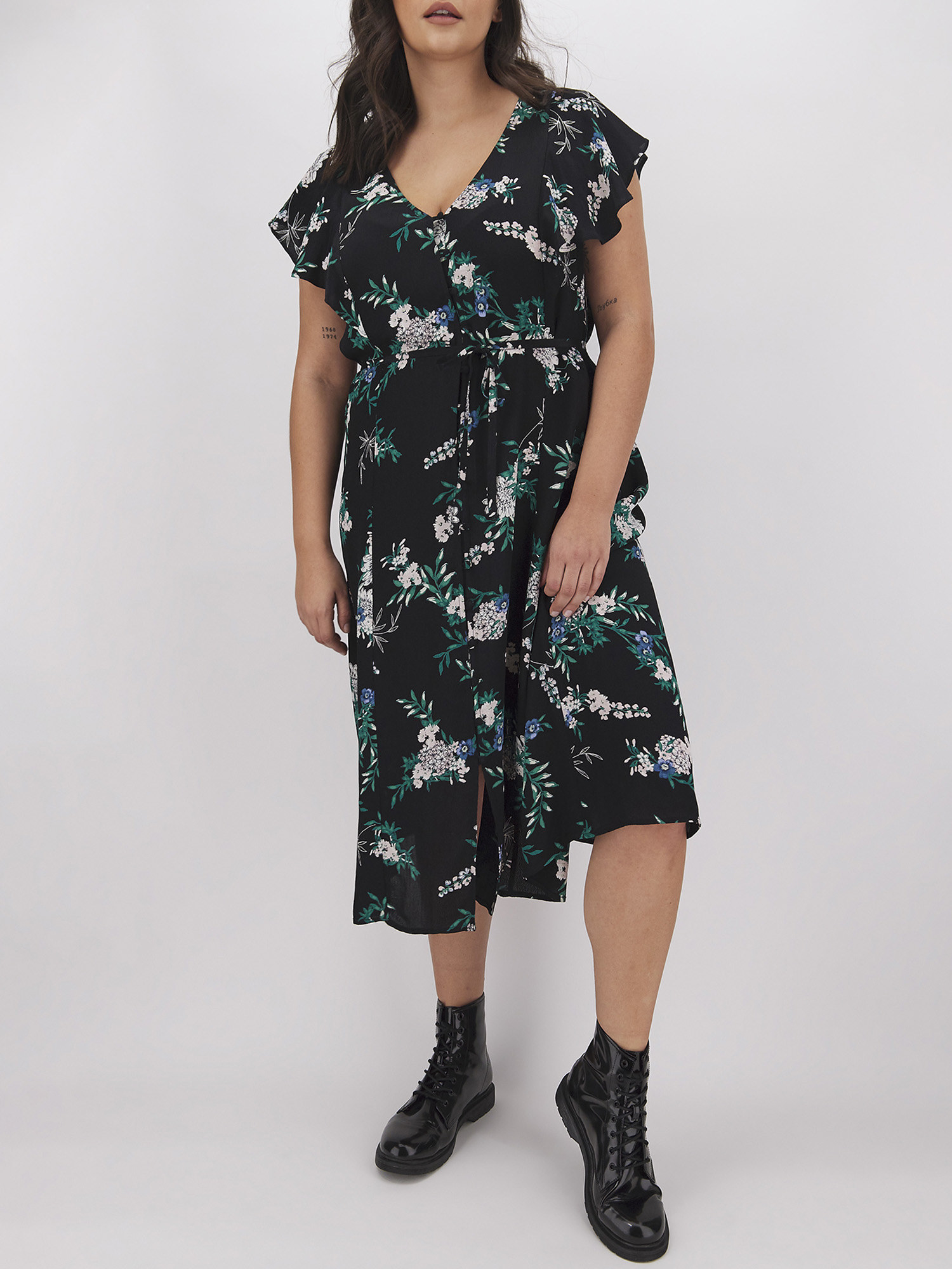 a model in the black dress with white and blue florals on it