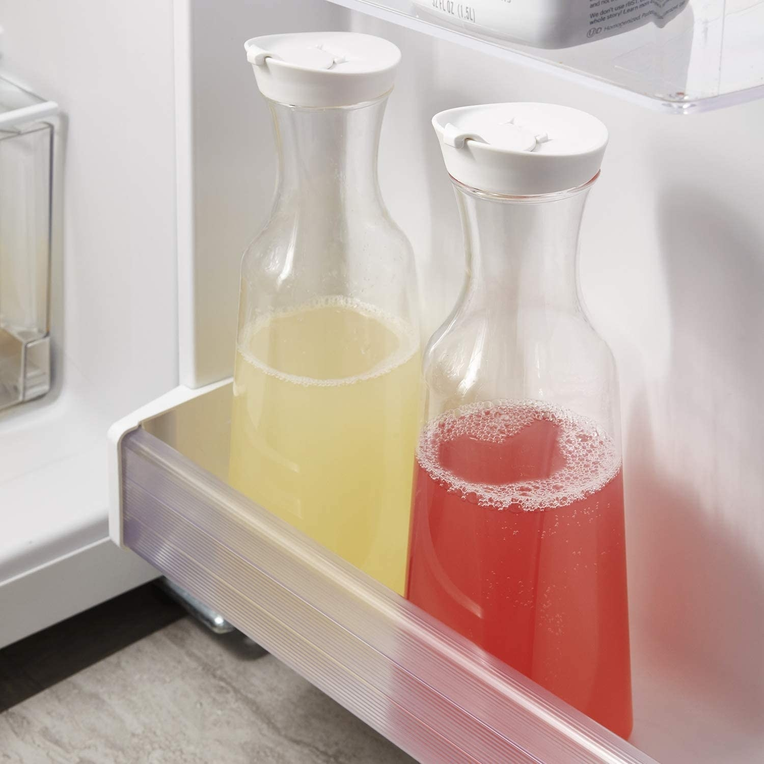 two tall carafes in square shape at bottom with lids in a fridge door