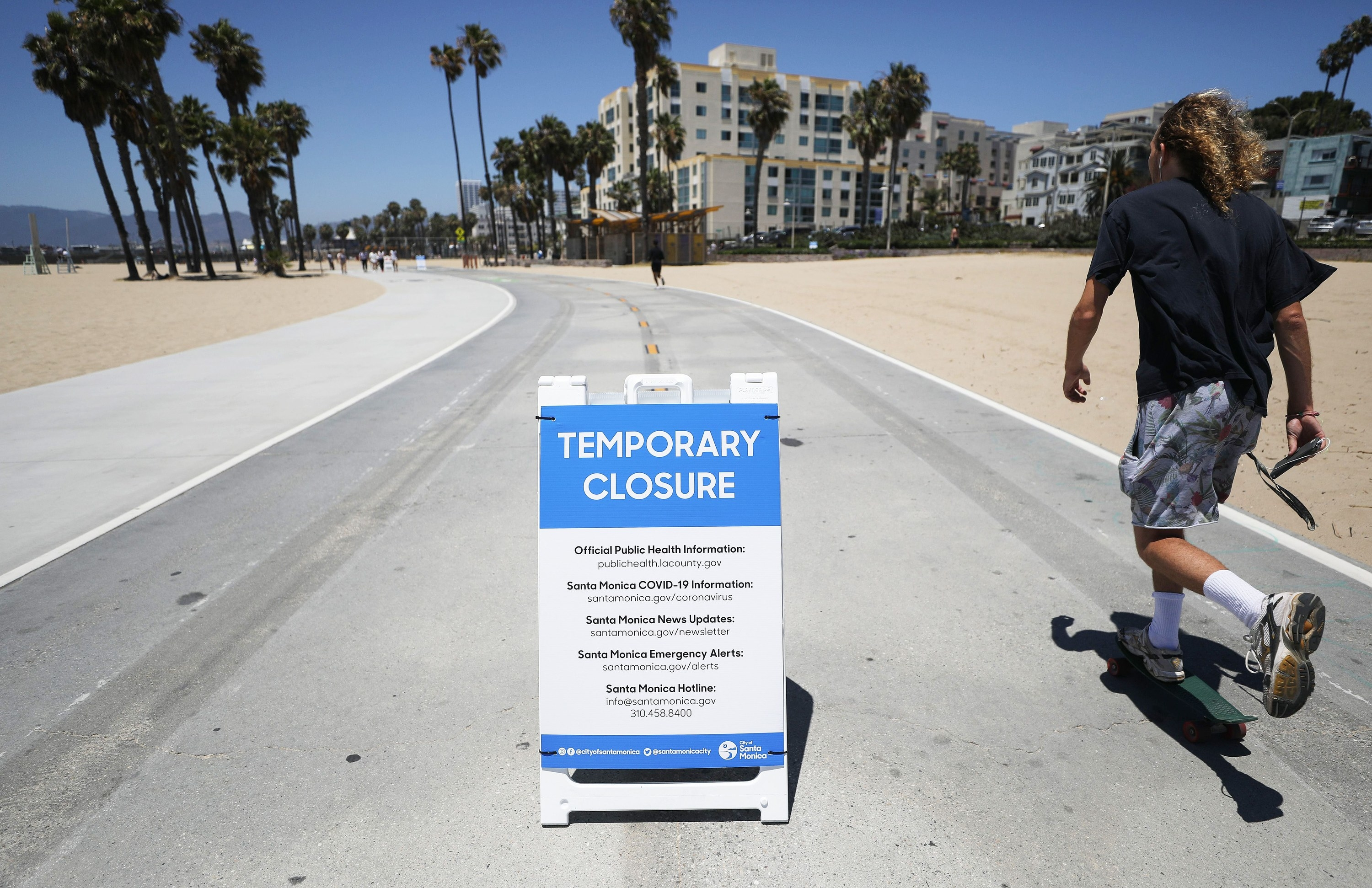A man skates by a notice of the beach's temporary closure