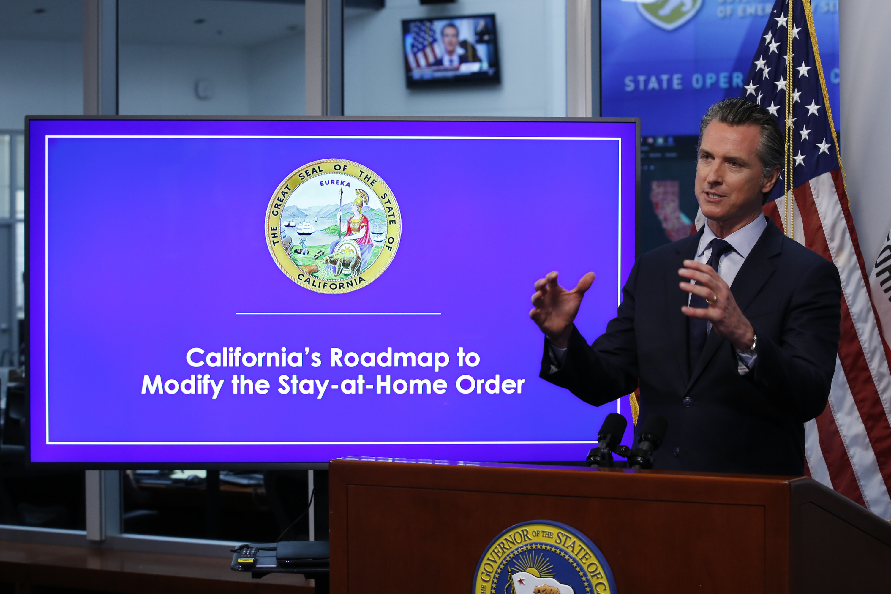 "Gavin Newsom, governor of California, stands behind a lectern and gives a speech in front of a large monitor that reads ""California's Roadmap to Modify the Stay-at-Home order"""