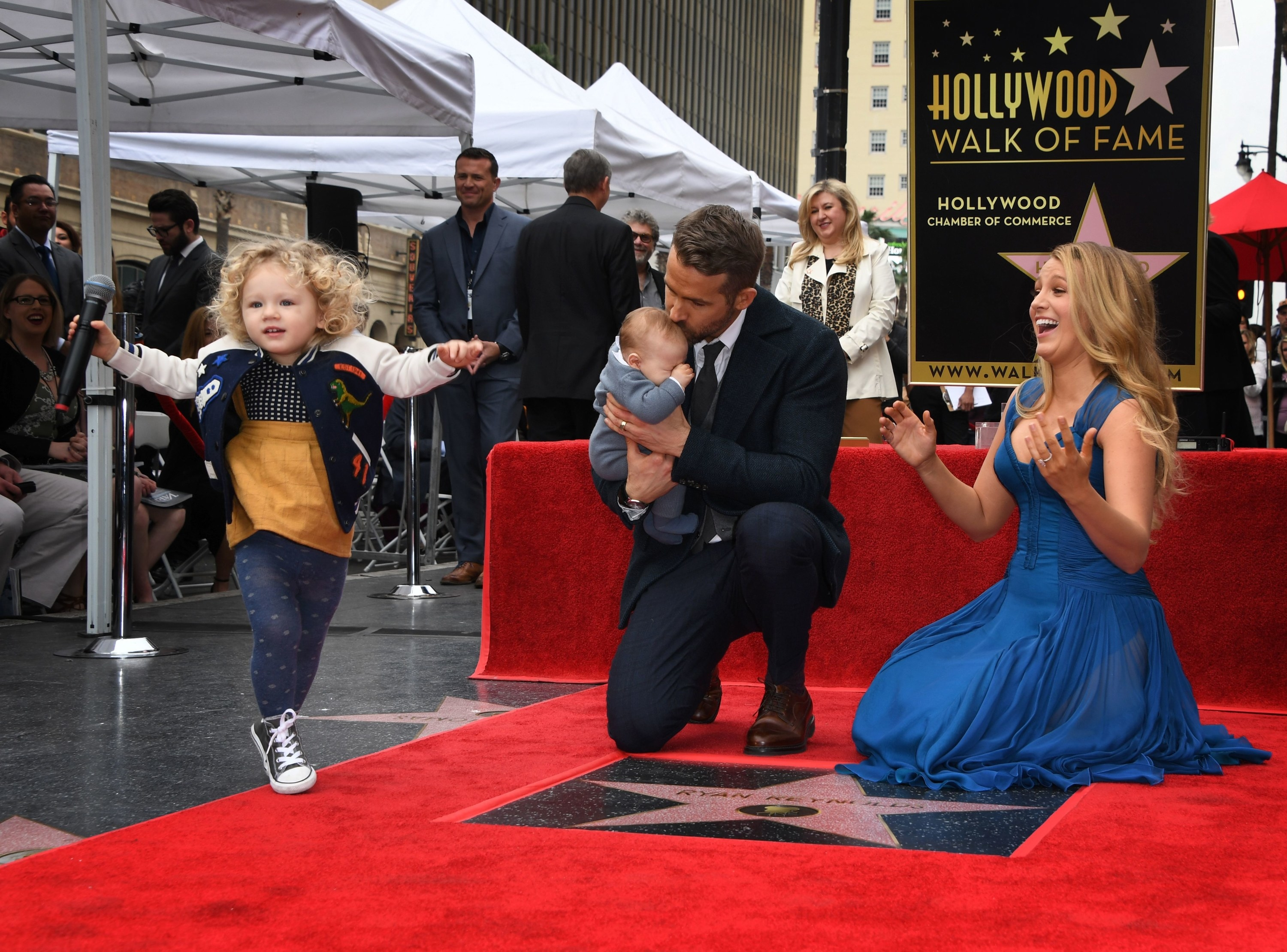 Ryan Reynolds, dressed in a suit, and Blake Likely, in a blue dress, kneel on the Hollywood Walk of Fame above Reynolds' star; Reynolds holds a baby as another child jumps onto a red carpet