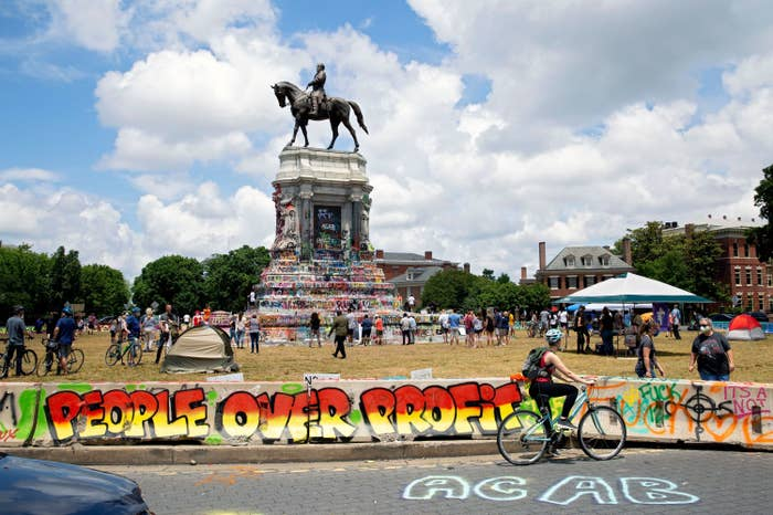 "Graffiti reading ""People Over Profit"" is on a small barrier near grass surrounding the enormous statue of Robert E. Lee riding a horse. People surround the statue on bikes and in tent as the sun shines through clouds."
