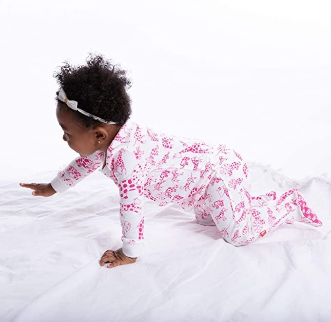 A baby model crawling in some white and pink animal print footie pjs