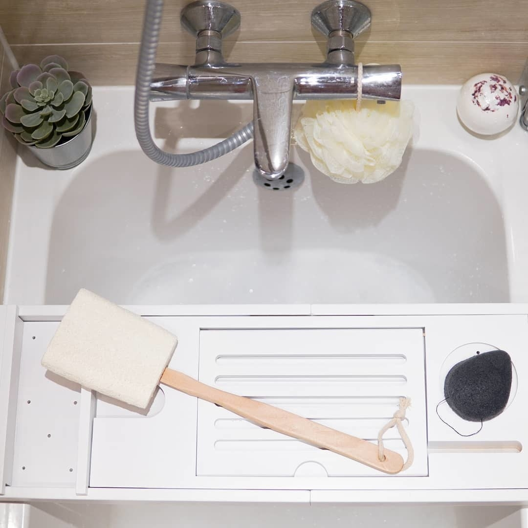 A loofah sponge attached to a long wooden handle sitting on a bath tray