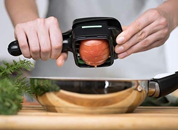 Hands slicing an onion with the food chopper