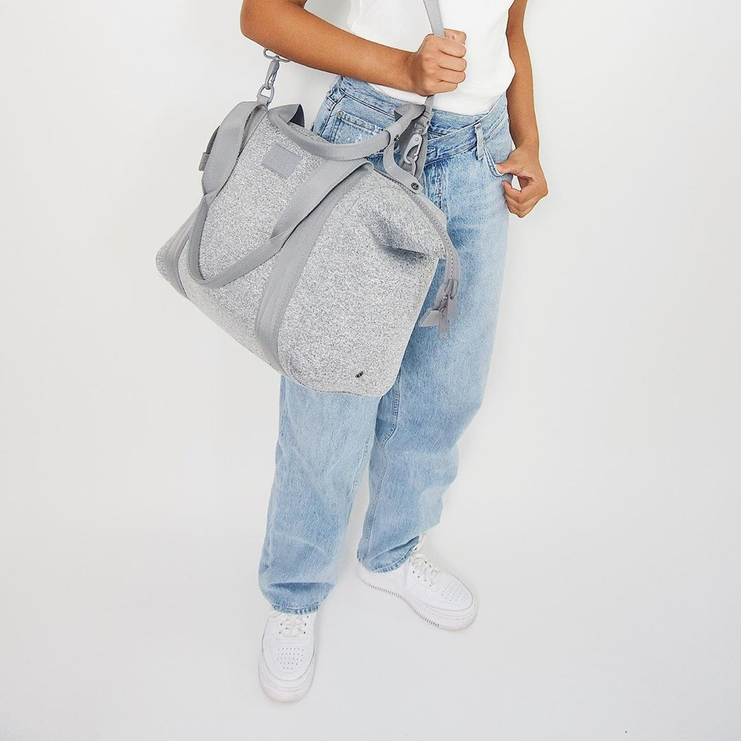 Model wearing the duffle bag on their shoulder using the long shoulder strap with a zipper across the top and shorter straps on the bag in heather grey