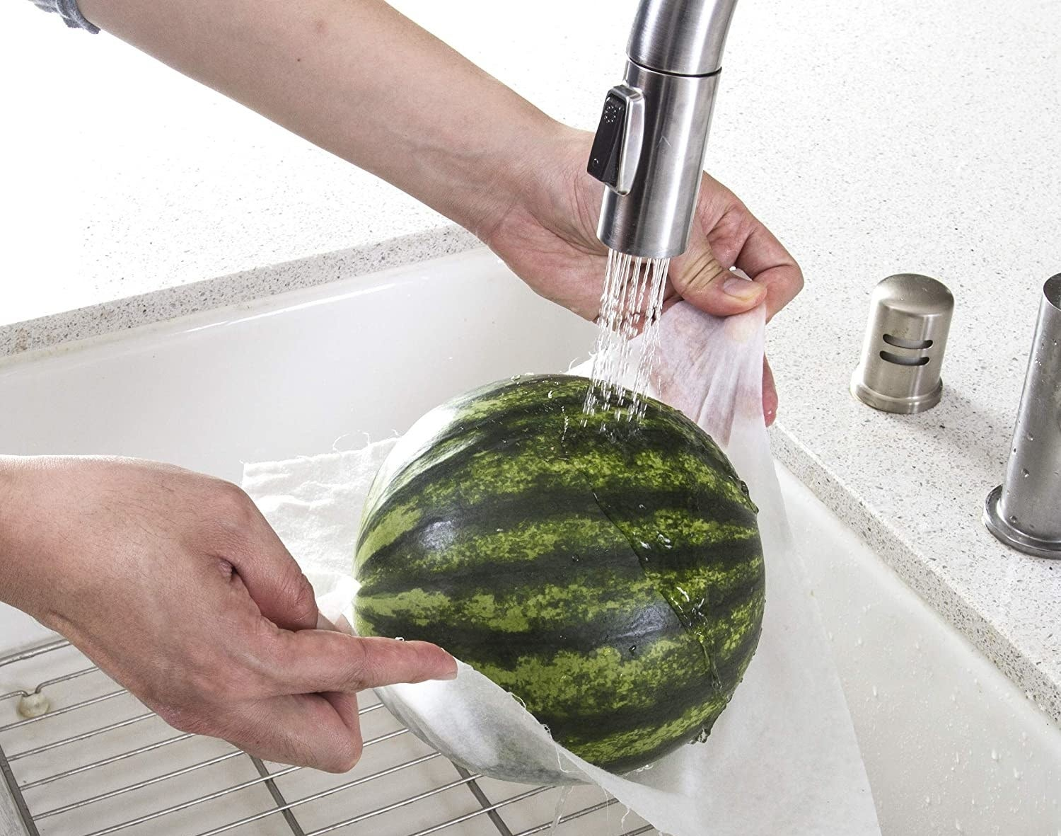 Model's hands holding a small watermelon in bamboo towel under running water