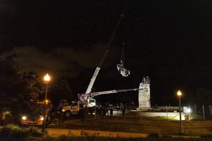 A crane removes a Christoper Columbus statue from its plinth amid nighttime darkness.