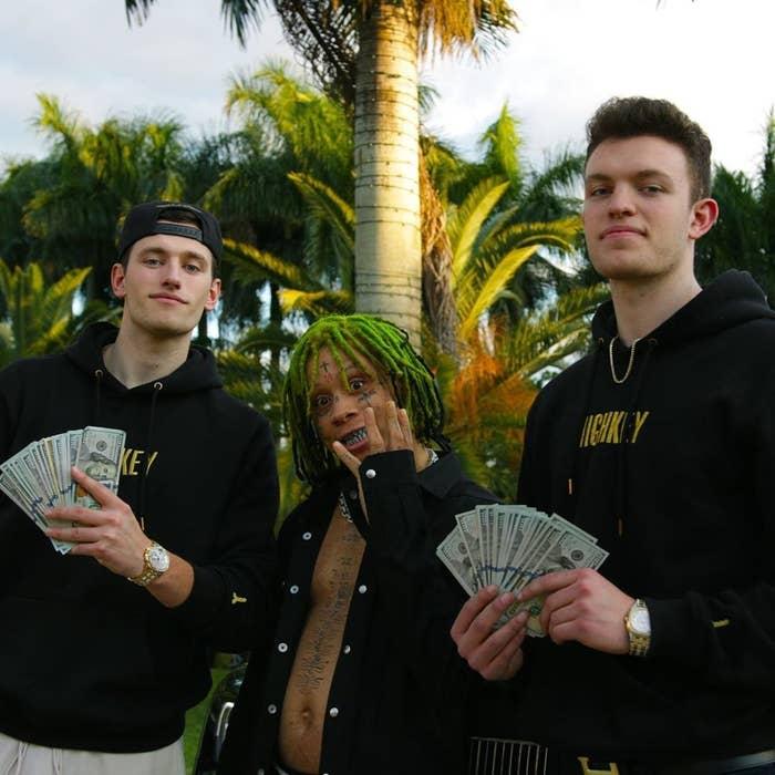 Trippie Redd standing beside brothers, Jordan and Luke Lintz holding stacks of Benjamins