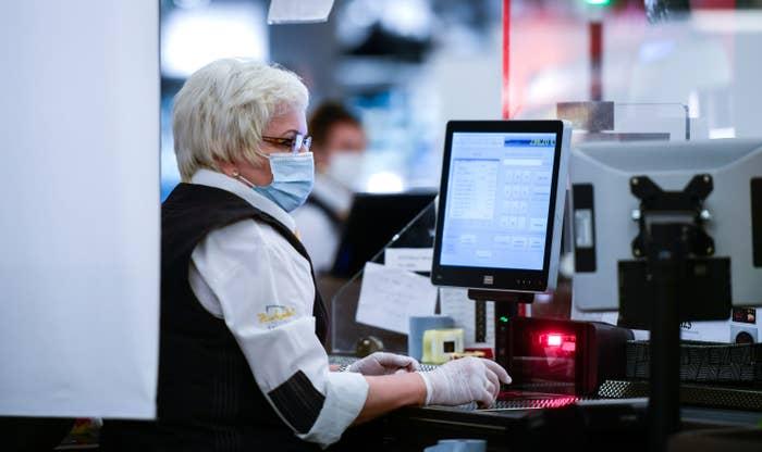 Eine Kassiererin sitzt mit Mundschutz und Handschuhen an einer Edeka-Kasse.