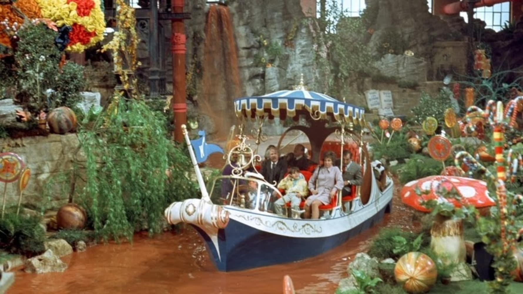 The cast glides down Willy Wonka's chocolate river in a boat