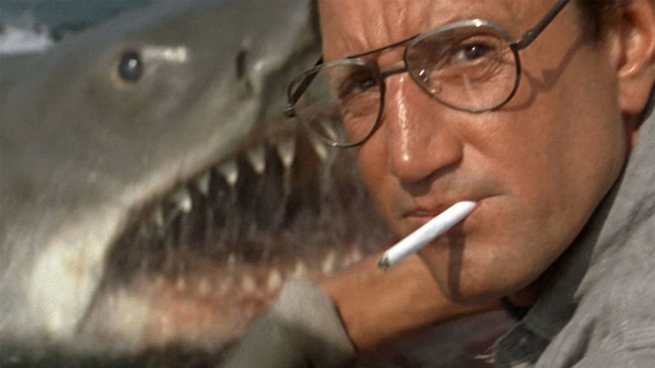 A man with glasses and a cigarette in his mouth looks at camera as a shark jumps up behind him