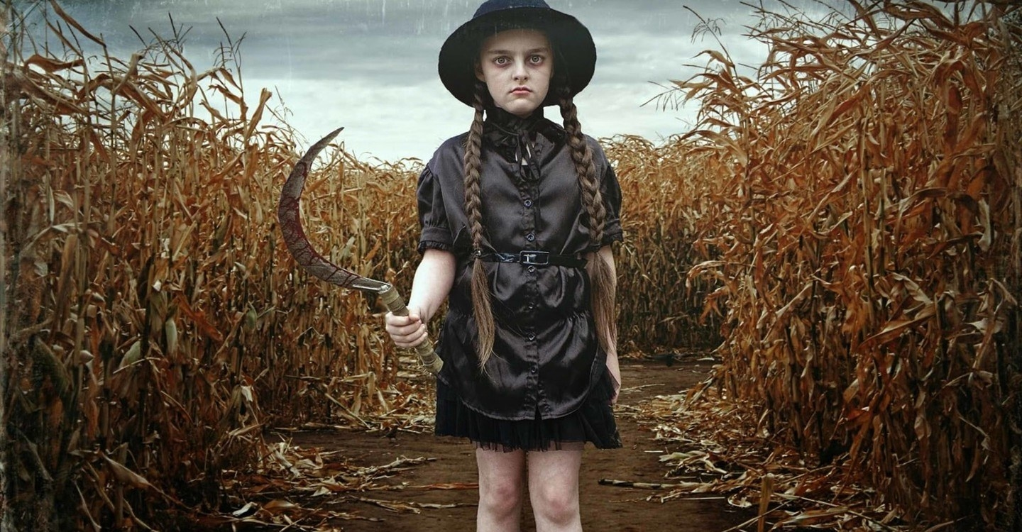 A young creepy girl with long braids and a sharp weapon walks through a cornfield