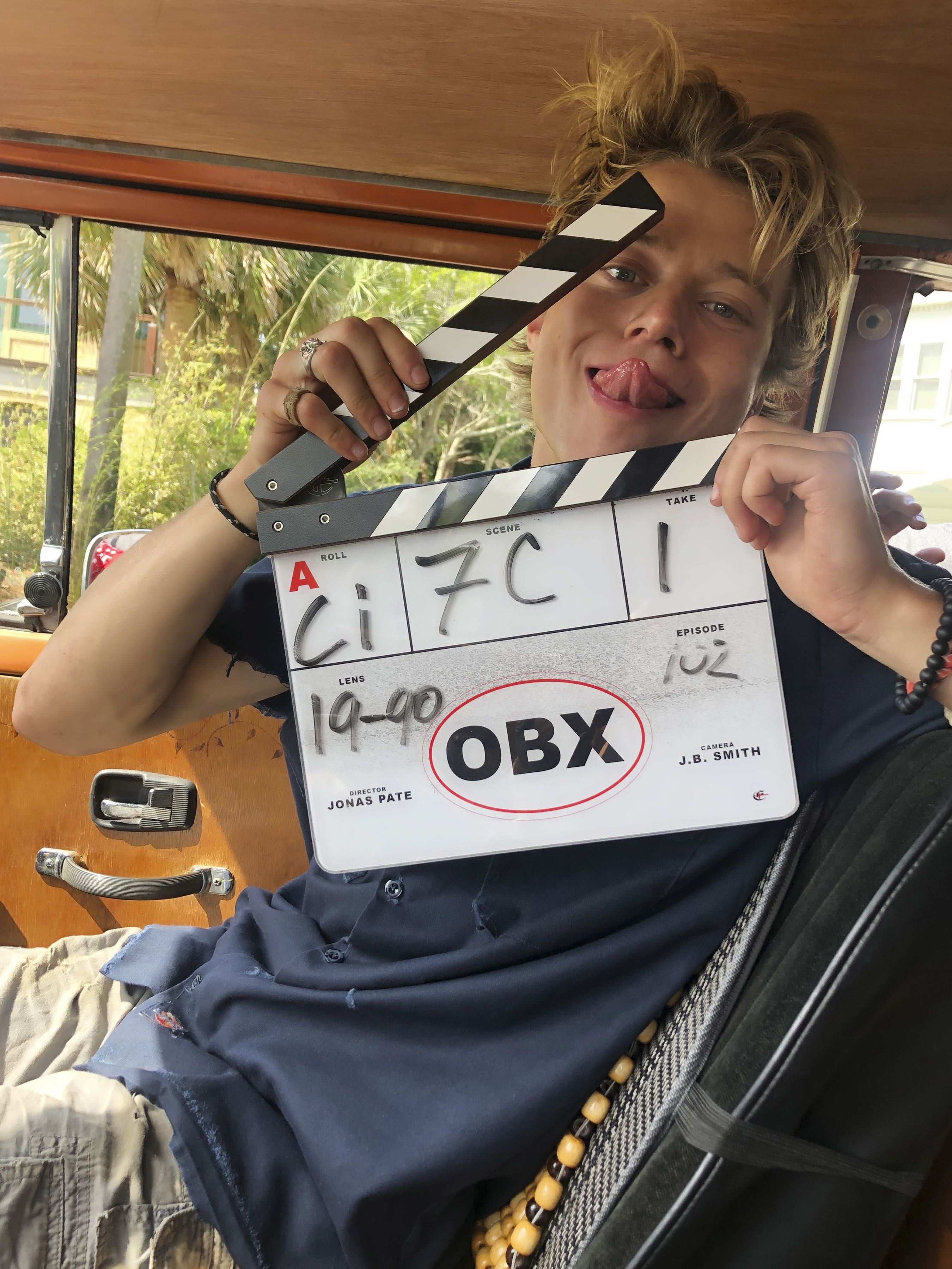 Rudy Pankow sticking his tongue out with a clapboard behind the scenes of Outer Banks