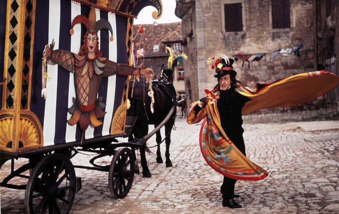 The Child Catcher, a man with a carnival hat and cloak, stands outside his horse and carriage