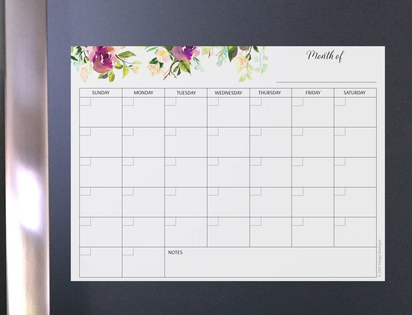 A blank white calender with floral designs on a refrigerator